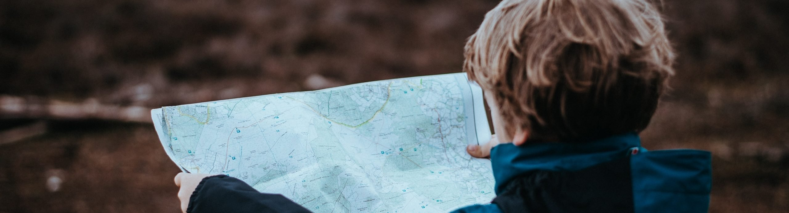 blonde kid reading map in woods